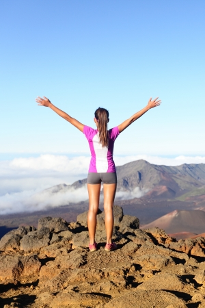 top of the world: Success and achievement - hiking woman on top of the world. Happy cheering woman in winning gesture, excited having reached summit of mountain, East Maui Volcano, Haleakala national park, Hawaii.
