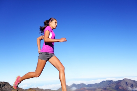 Running sports fitness runner woman jogging. Female athlete training outdoor under blue sky in amazing nature. Multiracial Asian Caucasian female fitness model exercising healthy lifestyle outside. Stock Photo - 22736708