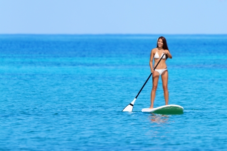 paddleboard: Stand up paddle board woman paddleboarding on Hawaii standing happy on paddleboard on blue water. Young mixed race Asian Caucasian female model on Hawaiian beach on summer holidays vacation travel.
