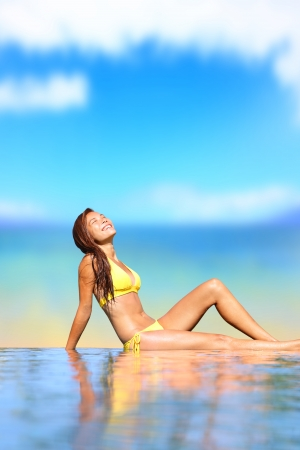Pool woman in bikini. Holiday travel image of beautiful young woman in bikini sitting by pool smiling happy and joyful in tropical beach resort. Beautiful mixed race Caucasian Asian female bikini model outside. Stock Photo