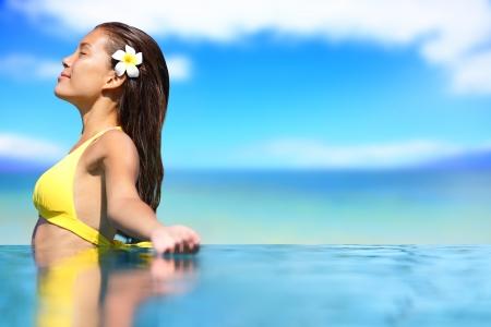 Relaxing serene woman at travel spa resort pool. Happy blissful asian young woman in bikini enjoying sun on holidays on Hawaii. photo
