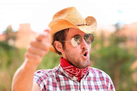 Cowboy man with sunglasses and cowboy hat pointing at camera saying WE WANT YOU. Male model in american rural western countryside landscape nature on ranch or farm, Utah, USA. photo