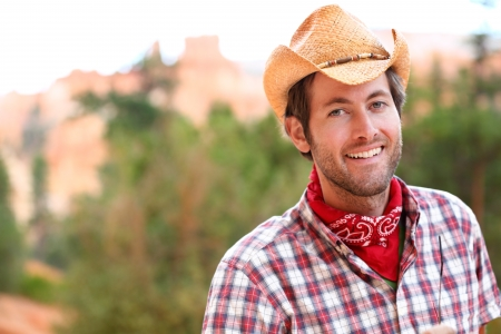 cowboy beard: Cowboy man smiling happy wearing hat in rural USA. Male model in american western countryside landscape nature on ranch or farm, Utah, USA. Stock Photo
