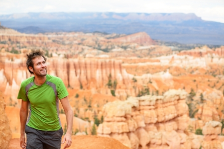 bryce: Hiker - man hiking in Bryce Canyon national park. Happy male outdoorsman walking enjoying outdoor activity walking in beautiful nature landscape in Utah, USA.
