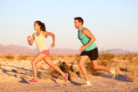 Cross-country trail running people at sunset. Runner couple exercising outside as part of healthy lifestyle. Multiracial runners couple, Asian woman, Caucasian man working out together.
