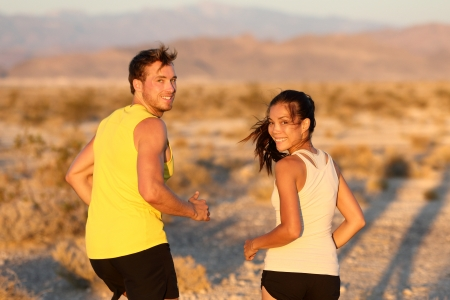Exercise - couple running looking happy at camera. Runners jogging outside in cross-country trail run. Fit young athlete man and woman fitness runner training together in prairie nature landscape, USA photo