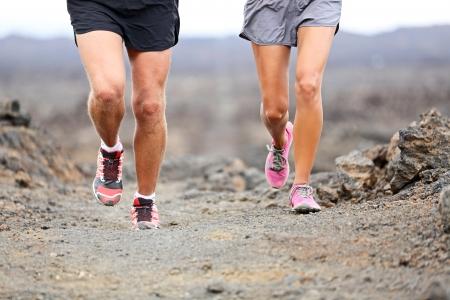 atleta corriendo: Carrera por monta�a - cerca de corredores zapatos y las piernas de los atletas que ejercen y esqu� de correr al aire libre en las rocas en el camino volc�n. La mujer y el hombre de la secci�n inferior de cerca. Foto de archivo