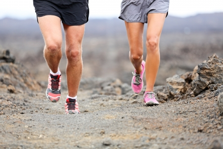 crosscountry: Trail running - close up of runners shoes and legs of athletes exercising and cross-country running outside on rocks on volcano path. Woman and man lower section closeup.