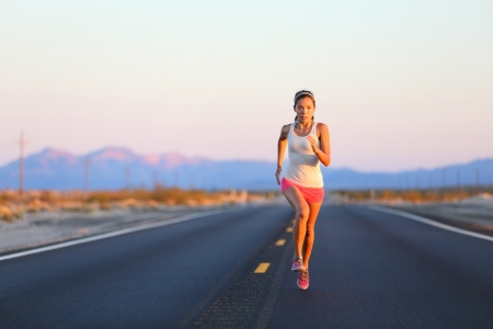 runner girl: Running woman sprinting on road highway at sunset at countryside in USA. Fit female fitness girl training outdoor in beautiful landscape. Multiracial Caucasian Asian female runner in her 20s.