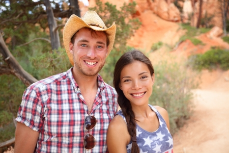 pocahontas: Happy outdoors couple portrait in american countryside. Smiling multiracial young couple in western USA nature. Man wearing cowboy hat and woman wearing USA flag shirt.