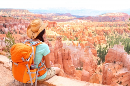 bryce: Hiker woman in Bryce Canyon hiking looking and enjoying view during her hike wearing hikers backpack. Bryce Canyon National Park landscape, Utah, United States.