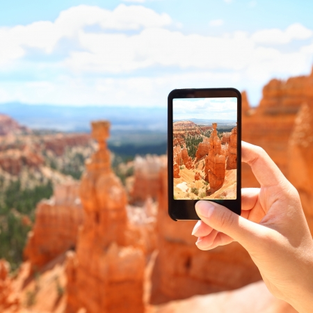 Smart phone camera taking photo picture of Bryce Canyon nature. Closeup of mobile phone camera screen photographing beautiful american landscape Bryce Canyon, Utah, United States. photo