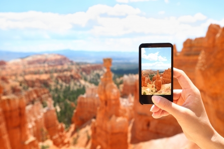 season photos: Smartphone camera phone taking photo picture of Bryce Canyon nature. Closeup of mobile phone camera screen photographing beautiful american landscape Bryce Canyon, Utah, USA. Stock Photo