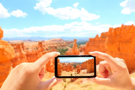 season photos: Smartphone taking photo of Bryce Canyon nature. Close up of mobile phone camera screen photographing beautiful american landscape Bryce Canyon, Utah, USA.