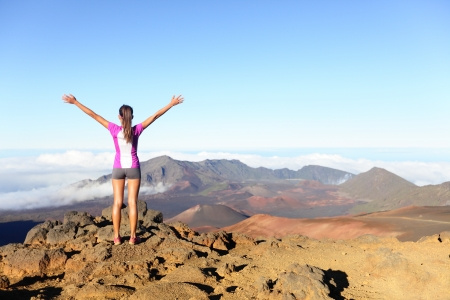 reach: Hiking woman on top happy and celebrating success. Female hiker on top of the world cheering in winning gesture having reached summit of mountain, East Maui Volcano, Haleakala national park Hawaii.