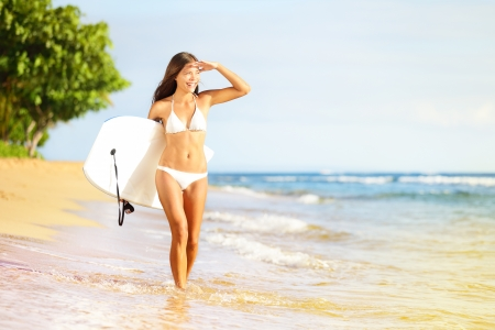 bodyboarding: Surfboard woman walking in beach water holding bodyboard. Beautiful surfer girl in white bikini going bodyboarding looking out over the sea enjoying sun. Mixed race Asian Caucasian, Maui, Hawaii, USA.