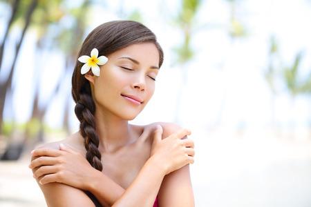 Spa wellness strand schoonheid vrouw ontspannen met de ogen sluit op Hawaii strand. Prachtige serene en rustige jonge gemengd ras Aziatische blanke vrouw model op vakantie vakantie resort. Bloem in gevlochten haar. Stockfoto