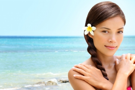 braided hair: Beach wellness spa beauty woman on Hawaii beach. Beautiful serene and peaceful young mixed race Asian Caucasian female model relaxing on holiday travel resort. Flower in dark braided hair.