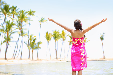 Praising happy freedom woman on beach wearing sarong stretching arms up, enjoying sun in worship and meditation zen. Serene girl seen from backside on Big Island, Hawaii, USA.