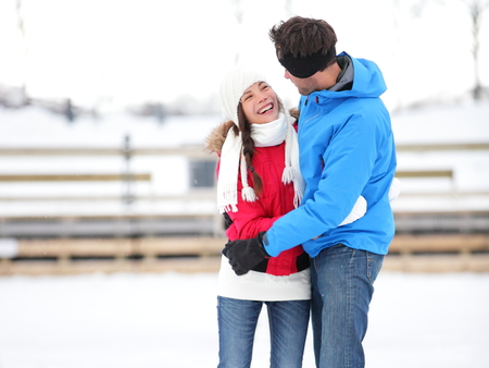 iceskating: Ice skating romantic couple on date iceskating embracing. Young couple holding hands on ice skates outdoors on open air rink in snowy winter landscape. Multiracial couple, Asian woman, caucasian man Stock Photo