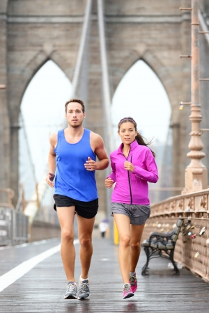 fit man: Running couple jogging training for New York marathon. Runners in rain outside. Asian woman and Caucasian man runner and fitness sport models jogging on Brooklyn Bridge, New York City, USA Stock Photo