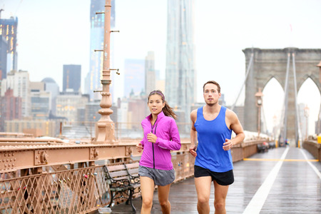 autumn city: Running couple. Runners jogging outside in rain. Asian woman and Caucasian man runner and fitness sport models training outdoor on Brooklyn Bridge, New York City, USA.