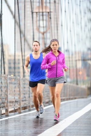 Running couple. Runners jogging outside in rain. Woman and man runner athletes training outdoor for marathon on Brooklyn Bridge, New York City, USA. Asian female and Caucasian male fitness sport model photo