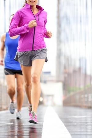 사람들을 실행 - 커플 조깅과 마라톤을위한 훈련. 비의 외부에있는 주자. 아시아 여자와 백인 남자 러너와 브루클린 다리, 뉴욕시, 미국에서 조깅 피트 스톡 콘텐츠