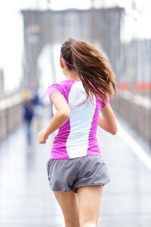アスリート: 市民ランナー - ブルックリン橋の上を走っている女性。背面ビュー裏面訓練外雨でニューヨーク、アメリカ合衆国の女性アスリートのクローズ アップ。 写真素材
