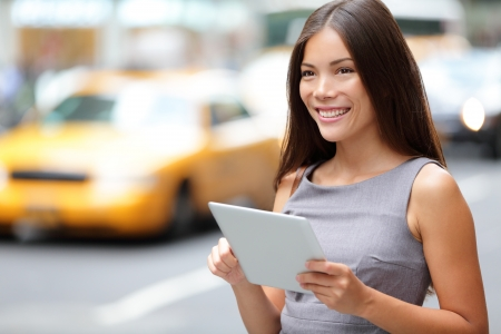 cab: Tablet computer business woman in New York City, standing in street with yellow taxi cab. Beautiful young professional businesswoman smiling happy. Mixed race female model in Manhattan, New York City.