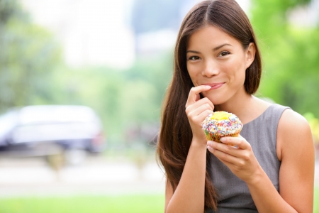 woman eat: Cupcakes - woman eating cupcake in New York, Central Park, Manhattan. Business woman eating unhealthy food snack in lunch break smiling happy. Beautiful casual businesswoman in New York City, USA.