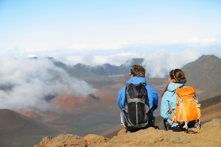 volcano: Hiking - hikers sitting enjoying view on volcano. Hiker couple looking at beautiful nature landscape of mountain, East Maui Volcano, Haleakala national park Hawaii, USA. People resting and relaxing. Stock Photo