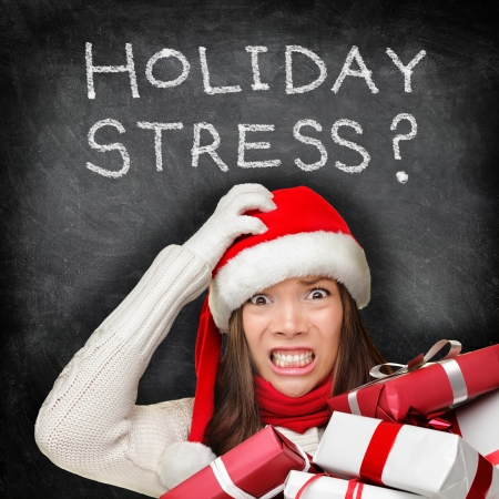 holiday: Christmas holiday stress. Stressed woman shopping for gifts holding christmas presents wearing red santa hat looking angry and distressed with funny expression on black chalkboard background.