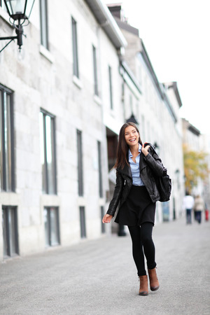 Urban modern woman outdoor walking in city street. Female fashion model wearing cool leather jacket and shoes outside. Happy ethnic Asian Caucasian girl in her twenties.