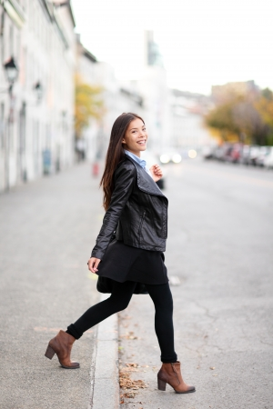 Fashion woman in city wearing urban leather jacket. Stylish female model walking in street crossing the road smiling happy. Multiracial Asian Caucasian girl in her 20s standing in full length outdoor. photo