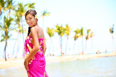 big island: Beach travel - woman smiling happy on Hawaii  Girl in sarong cheerful on sunny hawaiian palm tree beach on holiday resort vacation  Big Island, Hawaii, USA  Multicultural Asian Caucasian female model  Stock Photo