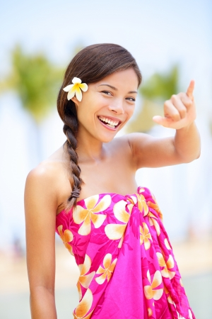 big island: Hawaii beach woman making Hawaiian shaka hand sign  Pretty and free asian girl enjoying vacation holiday on beach resort with palm trees  Mixed race female on Big Island, Hawaii Stock Photo