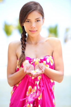 Beautiful serene woman on beach in sarong holding flower in palm of hands  Portrait of pretty graceful mixed race asian young woman on travel vacation on Hawaiian beach, Hawaii, Big Island, USA  photo