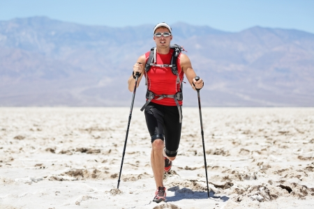 Ultra running man - trail runner in extreme race training for marathon. Fit male athlete running with trekking hiking poles in Death Valley, USA.