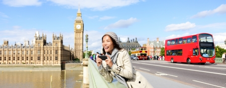 London travel banner with woman tourist, Big Ben and red double decker bus. Girl taking photo on Westminster Bridge with smartphone camera over River Thames, London, England, Great Britain, UK. photo