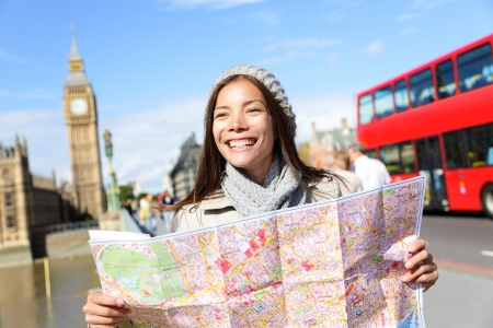 London tourist woman on Europe travel sightseeing holding map by Big Ben and red double decker bus. Tourism people concept with mixed race Asian girl smiling happy, Westminster Bridge, London, England photo