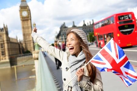 Londen - gelukkige toerist met Britse Britse vlag door Big Ben en rode dubbeldekker bus. Opgewekt meisje sightseeing op Westminster Bridge, Londen, Engeland, Verenigd Koninkrijk. Multiraciale Aziatische blanke