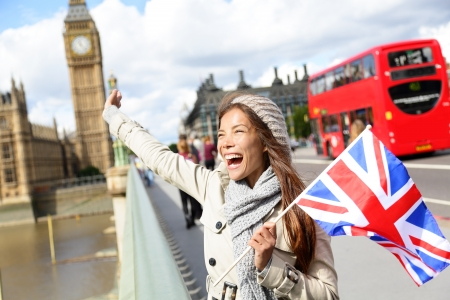 england: London - happy tourist holding British UK flag by Big Ben and red double decker bus. Excited girl sightseeing travel on Westminster Bridge, London, England, United Kingdom. Multiracial Asian Caucasian
