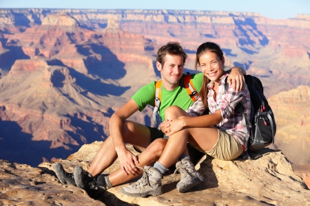 canyon: Hiking couple portrait - hikers in Grand Canyon enjoying view of nature landscape looking at camera smiling happy. Young couple trekking, relaxing after hike on south rim of Grand Canyon, Arizona, USA Stock Photo