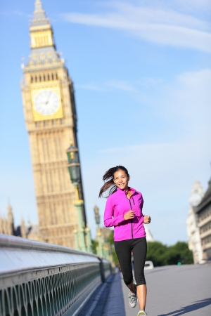 Woman running in London in front of Big Ben. Female runner on Westminster Bridge. Multicultural Asian Caucasian girl jogging training in London City, England, United Kingdom. photo