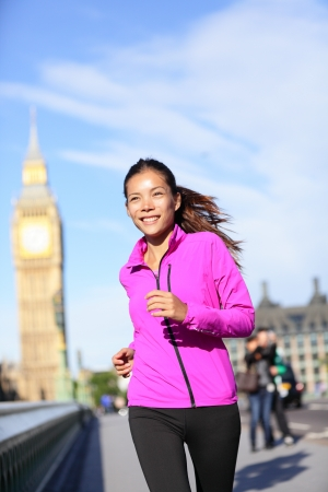 Running woman in London living healthy lifestyle. Female runner jogging near Big Ben in jacket. Urban fitness girl smiling happy working out on Westminster Bridge, London, England, United Kingdom. photo
