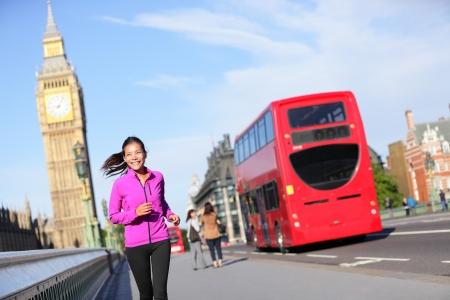 伦敦生活妇女跑在大本钟附近。女跑步者慢跑训练在城市与红色双层巴士。英国伦敦,威斯敏斯特桥上,健身女孩开心地微笑着。