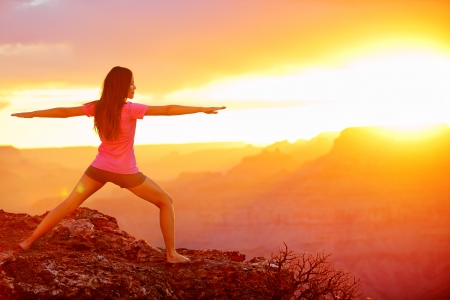 warrior: Yoga woman meditating at sunset in Grand Canyon. Female model meditating in serene harmony in warrior pose. Healthy wellness lifestyle image with multicultural young woman. From Grand Canyon, USA