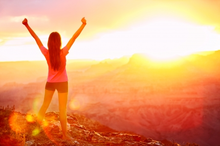 with raised: Freedom and adventure - woman happy in Grand Canyon. Free cheering girl with arms raised enjoying serene sunset in winning pose with arms stretched after hiking. Female model in Grand Canyon, USA. Stock Photo
