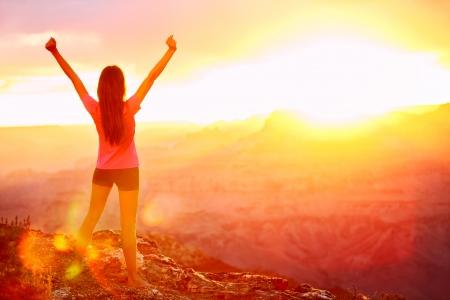 Wolność i przygoda - kobieta szczęśliwa w Grand Canyon. Bezpłatne doping dziewczyna z podniesionymi rękami korzystających spokojny zachód słońca w wygranej z rękami wyciągniętymi stanowią po wędrówki. Modelka w Grand Canyon, USA.